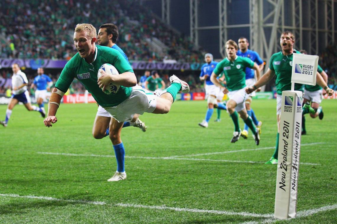 Ireland rugby player Keith Earls jumps over the line to score a try, his teammates looking on.