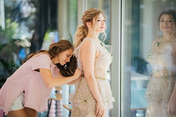 A woman bends to adjust the back of a bride's dress.