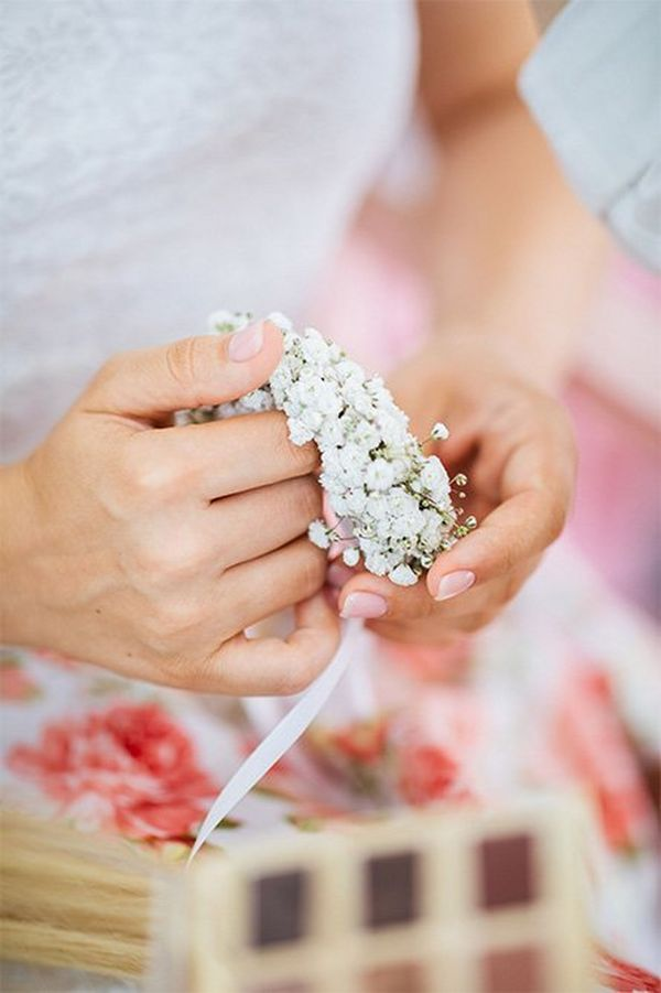 A close-up of hands holding bridal flowers.
