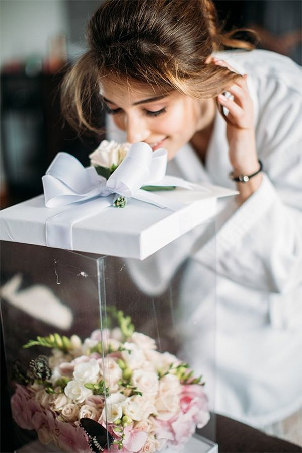 A woman in a white dressing gown bends over to sniff flowers on a box tied with a large bow.