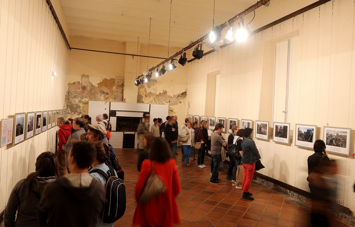 People walk around an exhibition room looking at the printed photographs on the walls.
