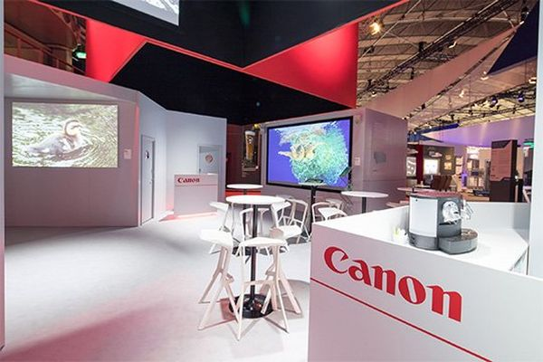 The Canon central area at the ISE trade show, with screens and tables.