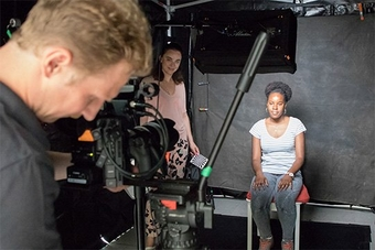 A young woman sits in a black-draped ready to be interviewed on camera.