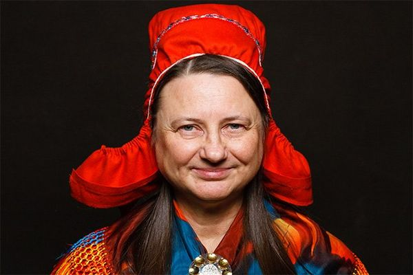 A Finnish woman in traditional costume with a red bonnet.