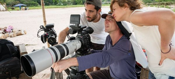 Two men and a woman look at the back of a Canon video camera with a long lens.