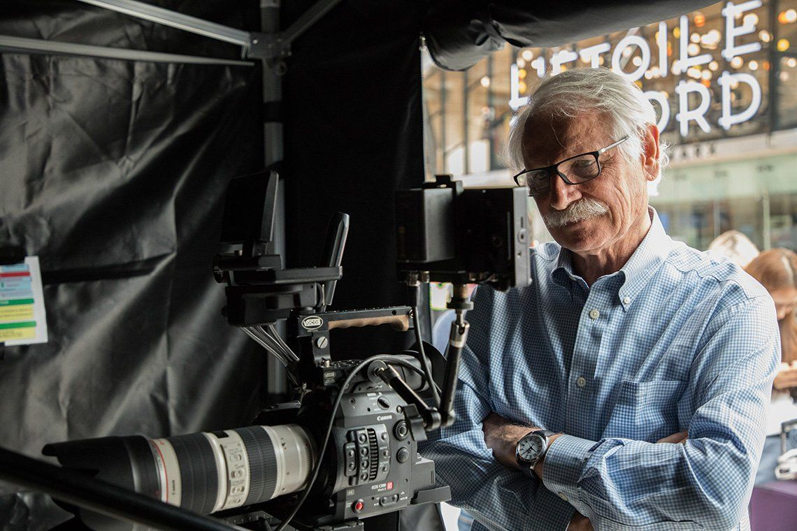 Yann Arthus-Bertrand looks at a monitor by a video camera.