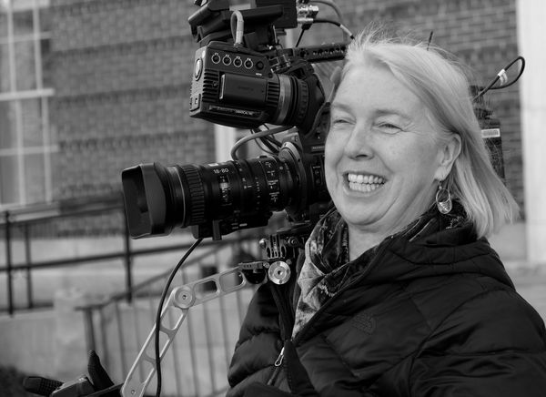 Cinematographer Claudia Raschke holding a cine camera.