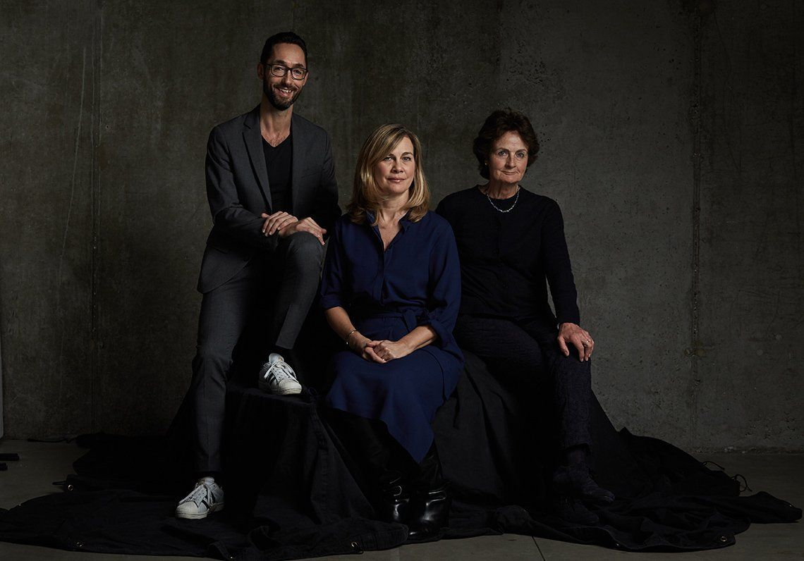 Thomas Borberg, Magdalena Herrera and Helen Gilks, all in smart clothing, sit against a grey backdrop on a black fabric-covered seat.