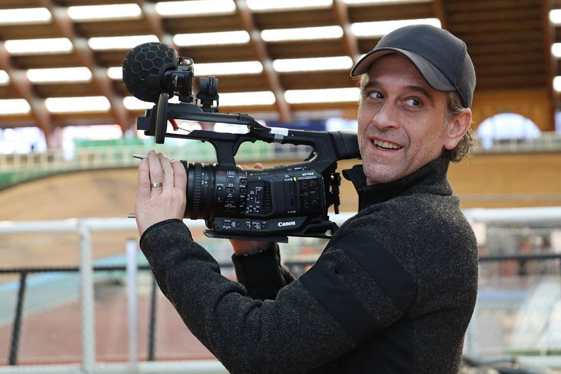 Filmmaker Sébastien Devaud holds a Canon XF705 camcorder to film, and smiles.