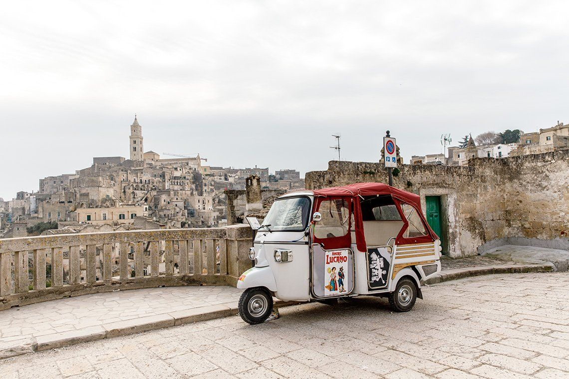 A tuk tuk parked in front of a balcony overlooking the Italian city of Matera. Photo by Annapurna Mellor with a Canon EF 24-70mm f/2.8L II USM.