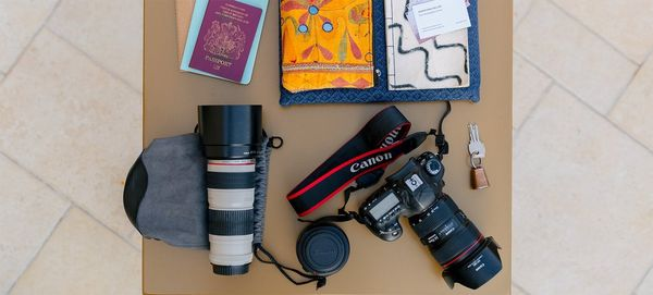 On a table sits a Canon DSLR, two Canon lenses, a passport and travel diary.
