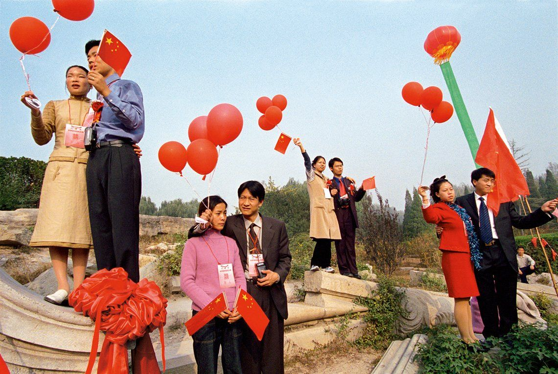 A wide shot of four couples holding red balloons, standing in the remains of an ancient palace.