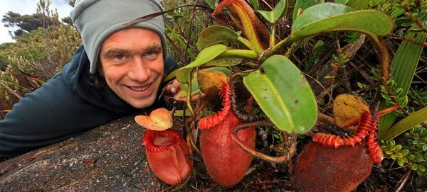 Photographer Christian Ziegler crouches low beside a red, carnivorous plant, smiling.