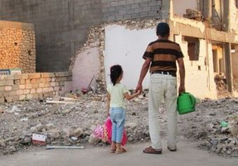 Image of young girl and her father looking at the rubble of the school.