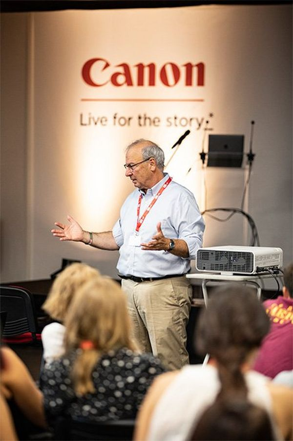 Francis Kohn stands on a Canon-branded stage, speaking to an audience.