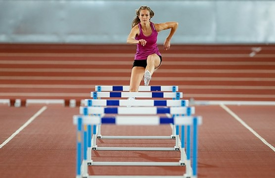 sports woman jumping over hurdles