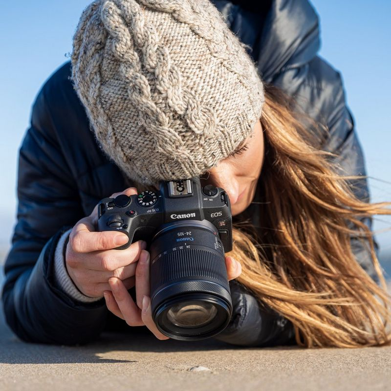 Lady wearing a grey beanie, blue coat and taking a shot on the EOS RP with RF 24-105mm F4-7.1 IS STM