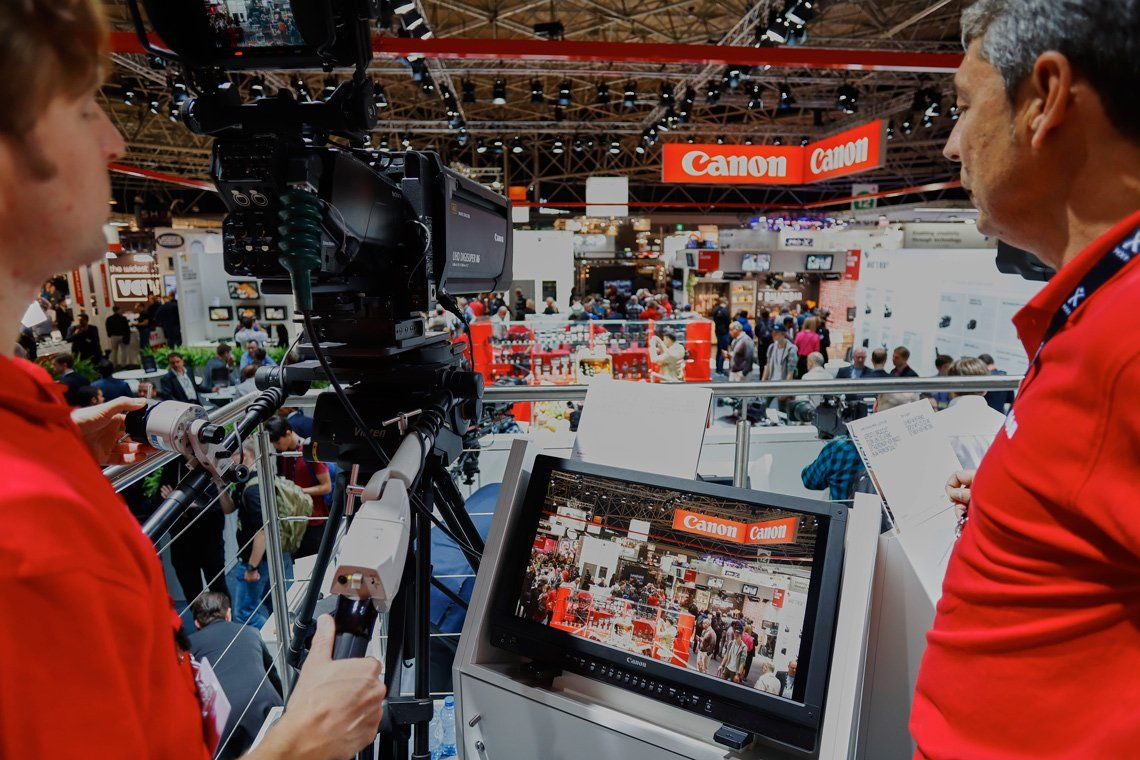 Canon staff overlooking IBC through a broadcast camera's lens on the Canon stand at the 2017 International Broadcasting Convention (IBC).