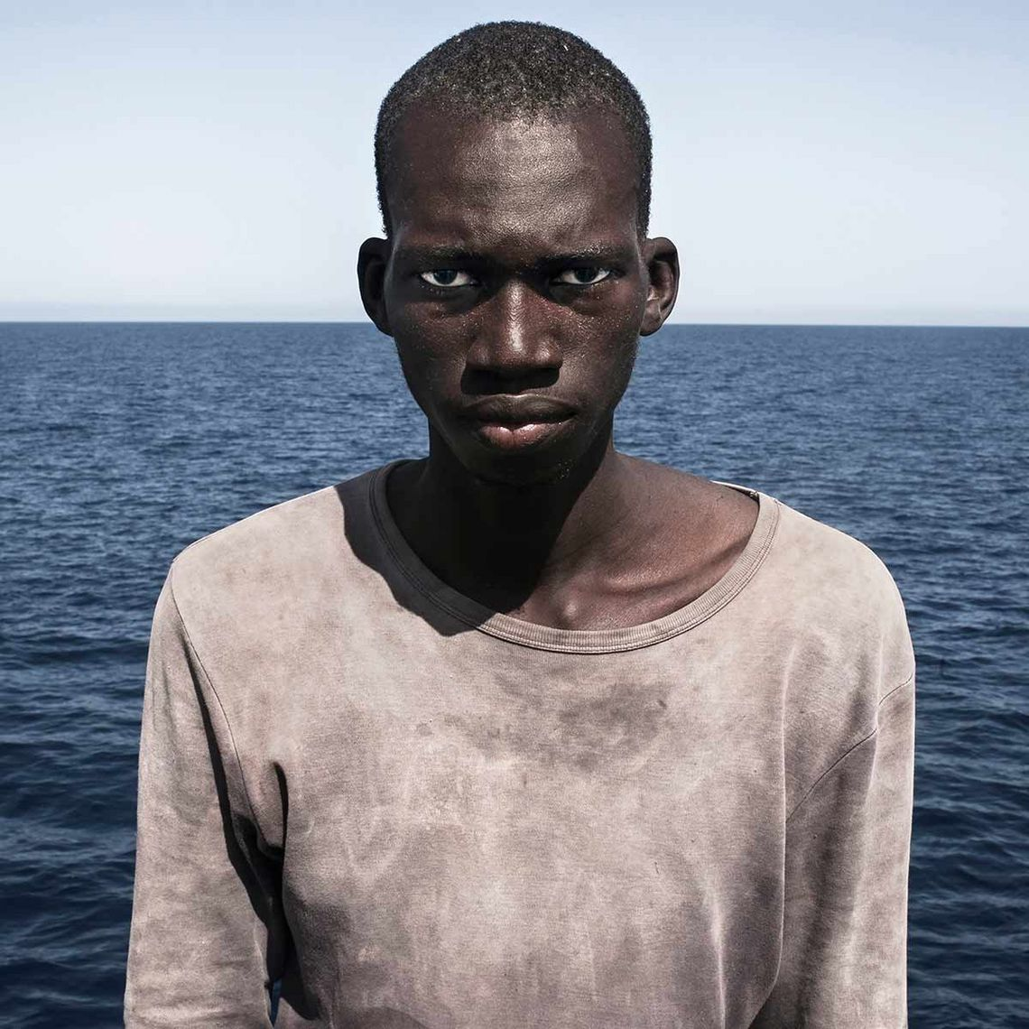 Brows furrowed, 23-year-old migrant Amadou Sumalia stares down the lens, minutes after being rescued from an overcrowded inflatable boat. He is aboard a German NGO vessel, the Iuventa, and the horizon of the Mediterranean can be seen in the backdrop.
