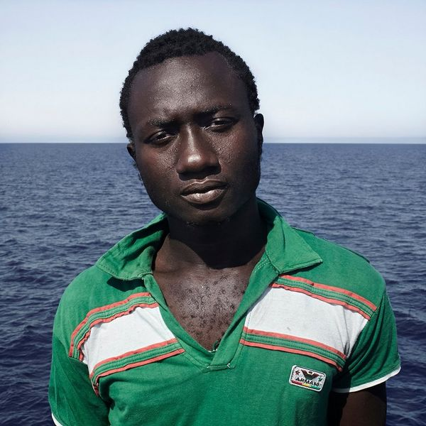 Enssa, aged 17, from Senegal, wears a emerald green tee-shirt aboard the Iuventa after coming aboard from the inflatable, black rubber rib he had been rescued from.