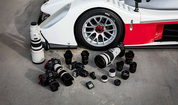 Three camera bodies and several lenses are laid out next to a sports car.