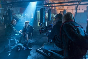 A boxer and trainer are lit from above by a shaft of light as they sit in a dim gym being filmed by a camera crew using a Canon EOS C700 FF.