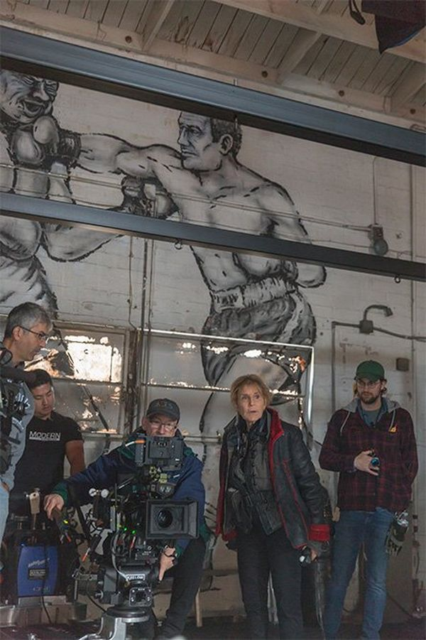 The camera crew at work in front of a large mural of a boxer landing a right cross on an opponent. Director Nigel Dick is seated behind a Canon EOS C700 FF, and cinematographer Nancy Schreiber stands to his left.