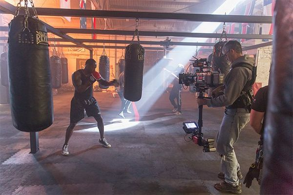 A camera operator with a Canon EOS C700 FF on a Steadicam films a boxer using one of several punching bags in a boxing gym.