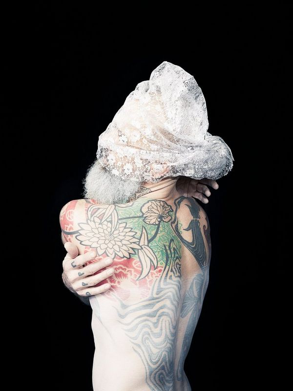Matthew, from Felicity McCabe's series Two Spirit. The bald, heavily tattooed man with a striking grey beard poses and wraps his arms around himself in the studio wearing a lace veil over his eyes.