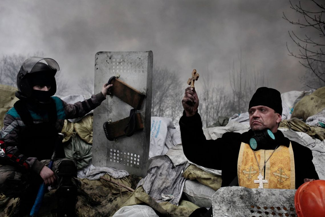 An Orthodox priest blesses protesters along a barricade in Kiev, Ukraine, during protests in 2014, captured by Jérôme Sessini. Unidentified snipers had opened fire on unarmed protesters, with an official sources suggesting 70 people were shot dead.