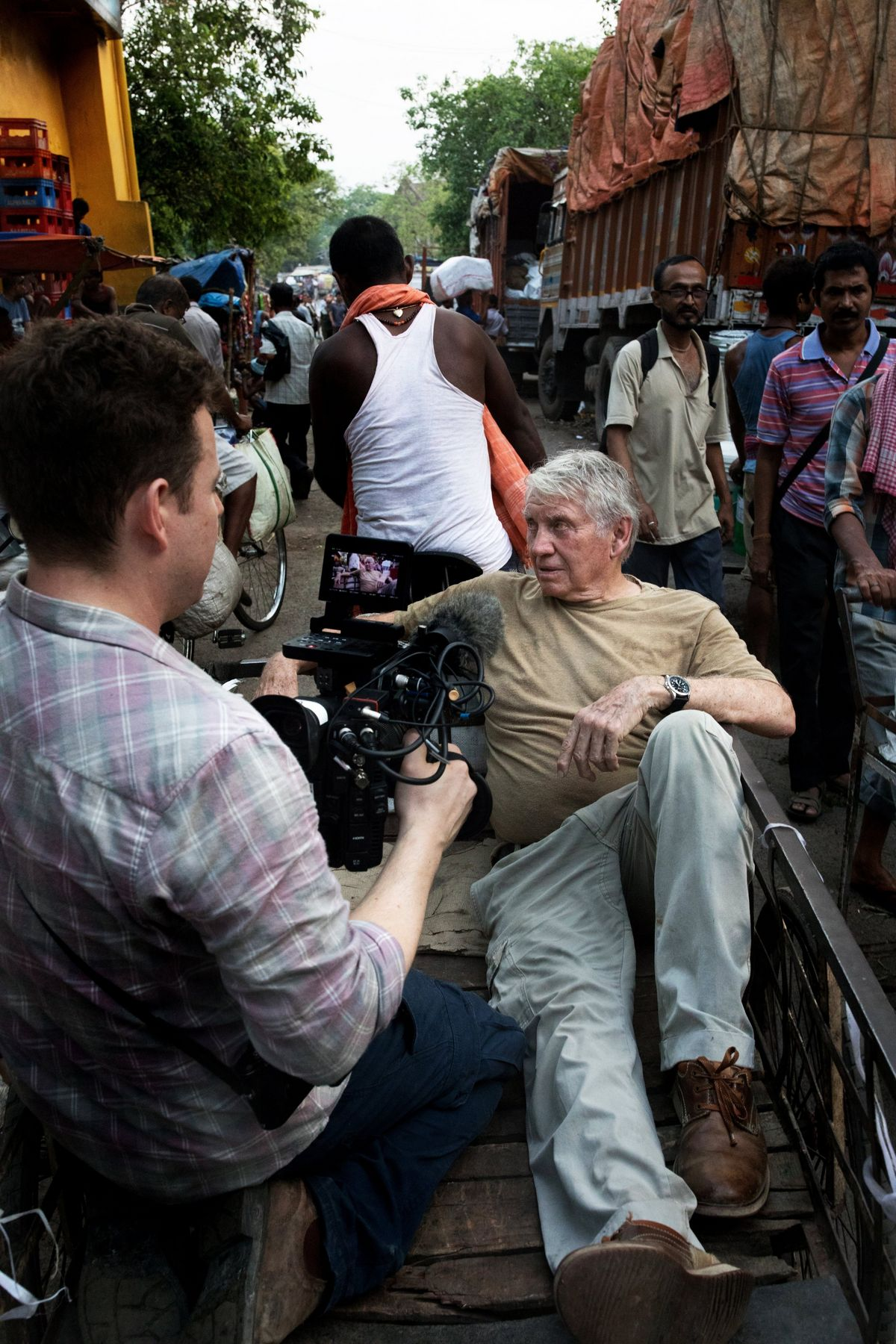 Cinematographer Chris Clarke films Sir Don McCullin through the streets of Kolkata.  © Lance Miller