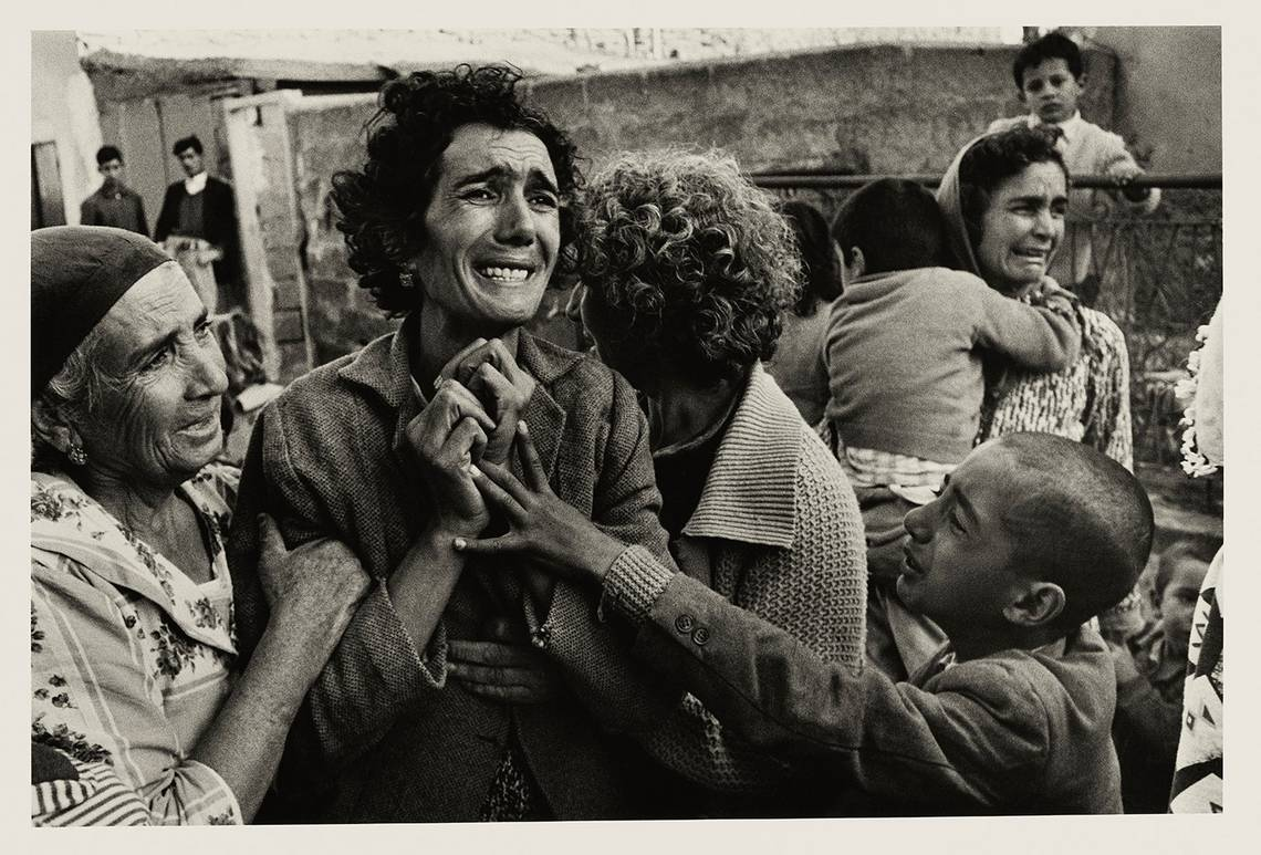 A grieving Turkish woman is comforted by others and clutches her hands to her chest as she mourns her husband, a victim of the Cyprus Civil War. In the background another woman can be seen weeping.