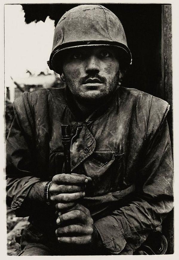 A shell-shocked US Marine gazes at the camera, dressed in army fatigues and clutching his rifle between his hands, in Sir Don McCullin's iconic shot of the Vietnam War.