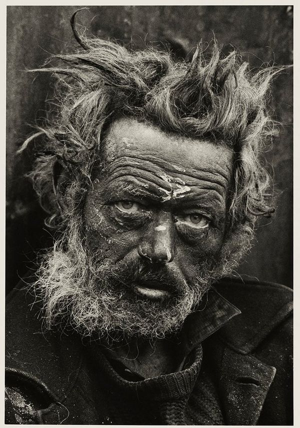 A homeless man from Ireland with bedraggled, grey hair sticking up in different directions, on the streets of the East End, London where he is living.