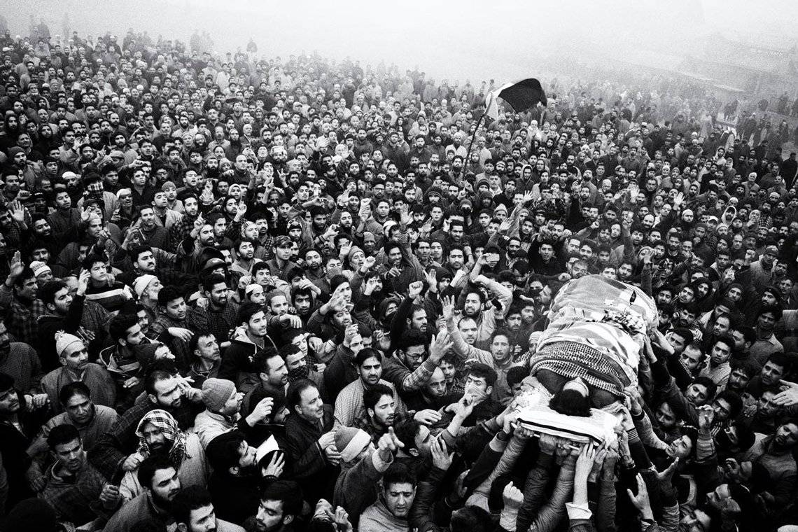 Kashmiri mourners shout slogans and wave the Pakistani flag while carrying the dead body of a militant.