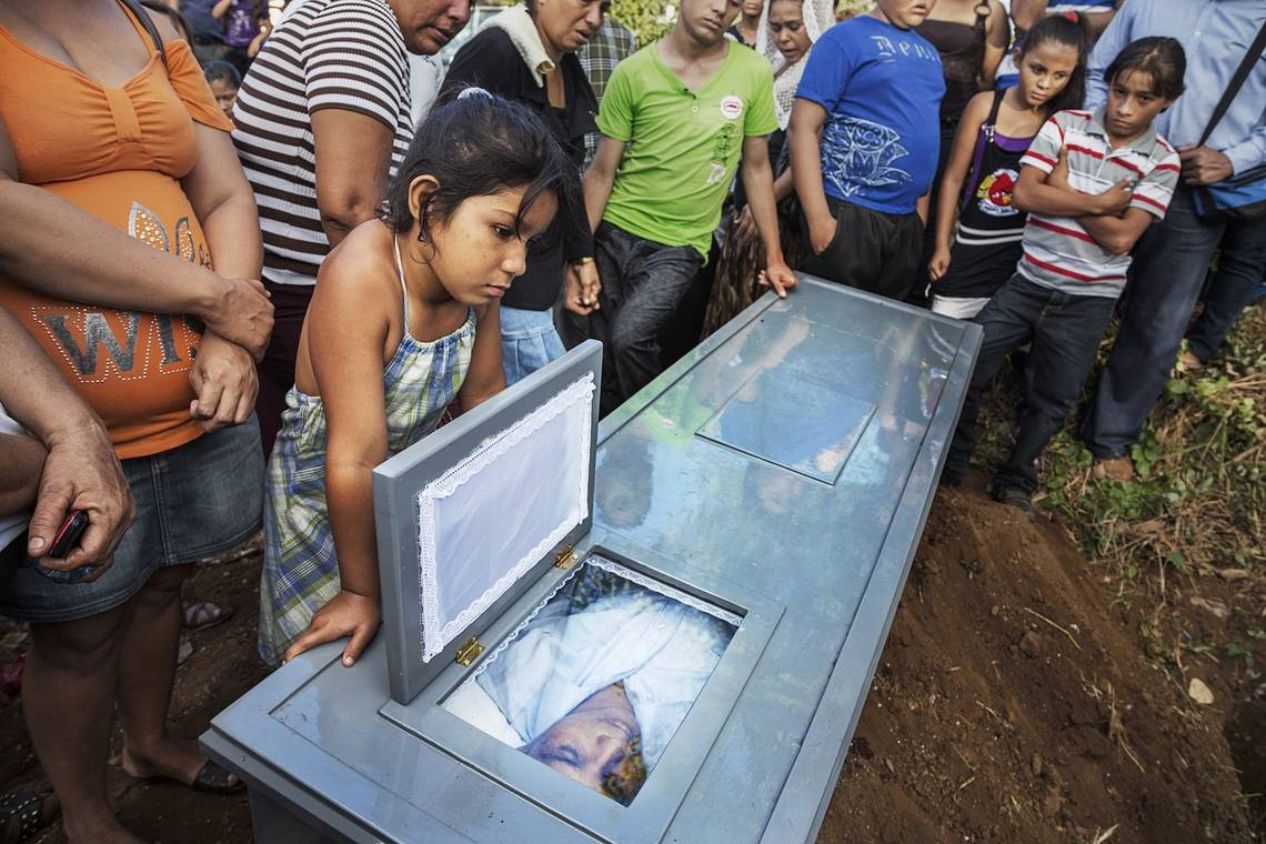 Family and friends gather at the graveside around the coffin of a former sugarcane worker in Chichigalpa, Nicaragua.