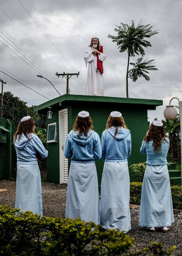 INRI Cristo preaches to his followers from the top of the compound guardhouse. The disciples live a quiet and secluded life inside the compound, growing most of their own food and focusing on INRI's mission. Shot on a Canon EOS 5D Mark III by Jonas Bendiksen.