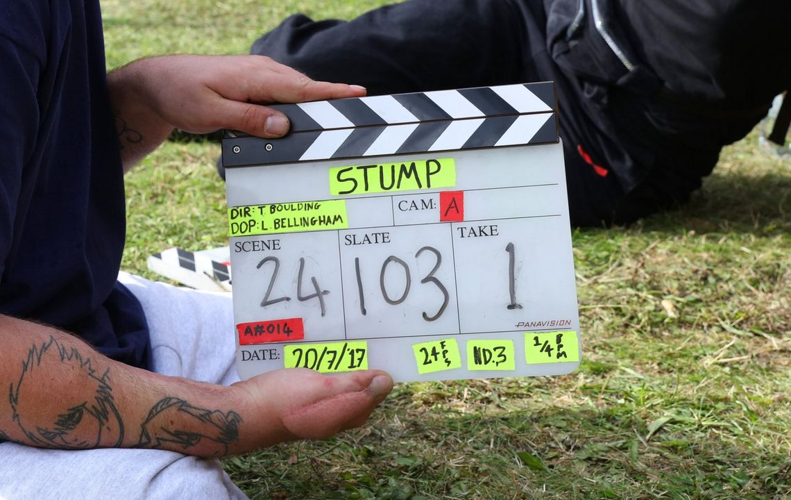 A close-up of a man holding a clapboard for Cam A with Scene 24 Slate 103 Take 1 written on it. He sits on grass and another person can be seen sitting on the grass behind him.