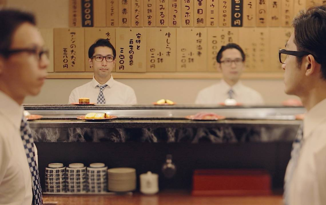 Japanese businessmen sitting in a kaiten-zushi watching sushi plates rotate on a conveyor belt.
