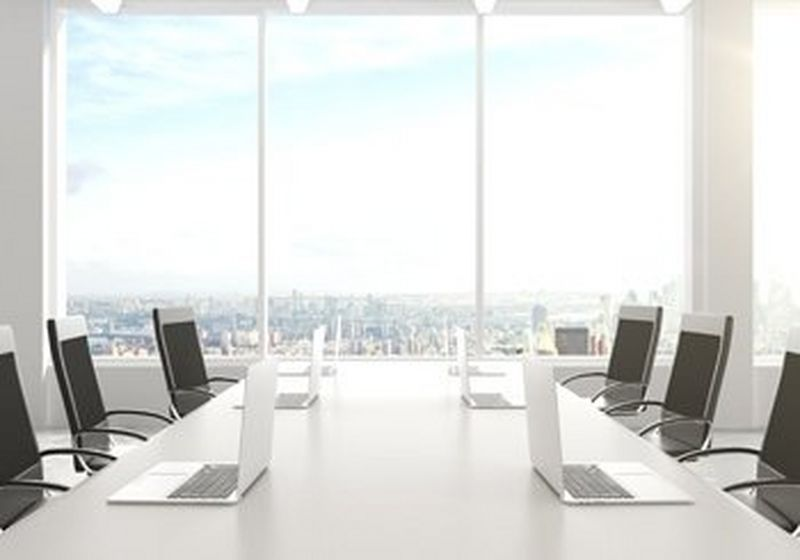A boardroom table with six chairs and six laptops, against a backdrop of a window, overlooking a city.
