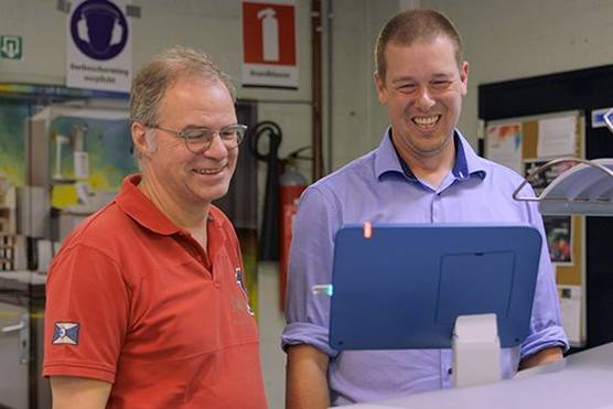 Two print professionals looking at print output from the VarioPrint i300