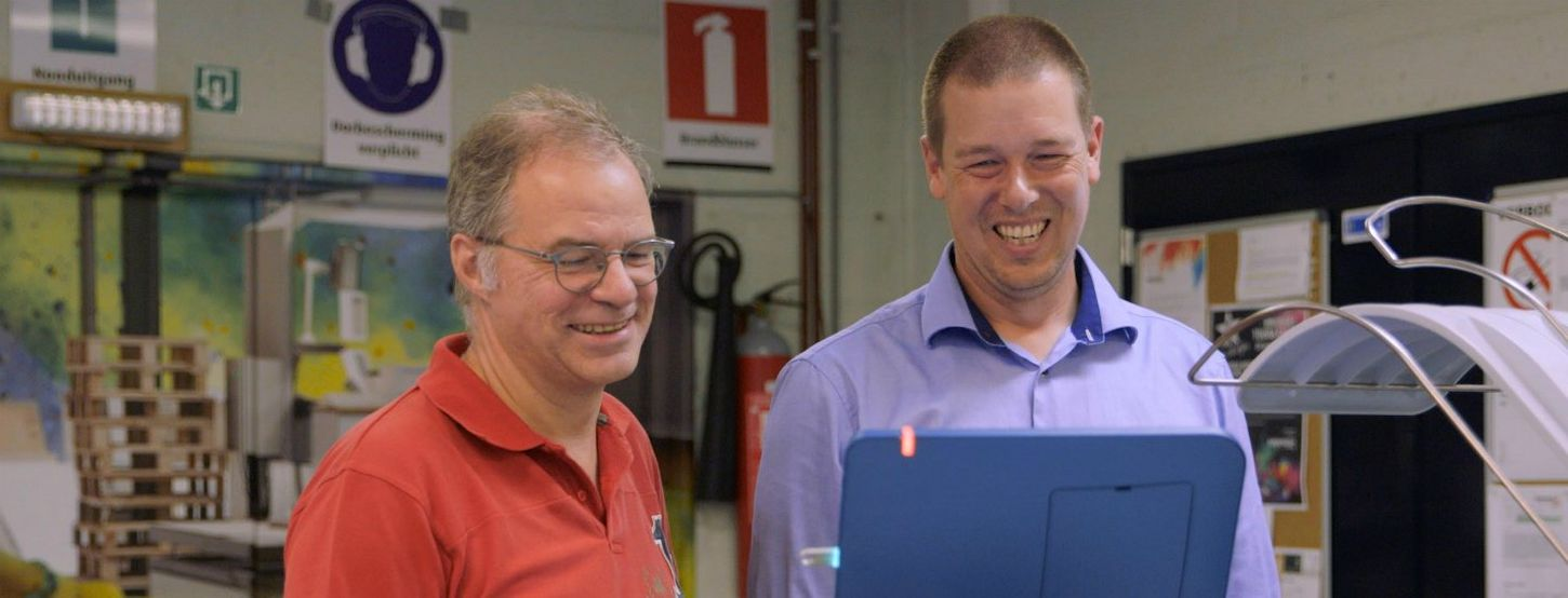 Older man wearing glasses and an orange polo shirt and younger man in blue long-sleeved shirt smile as they look at a screen on a commercial digital printer.