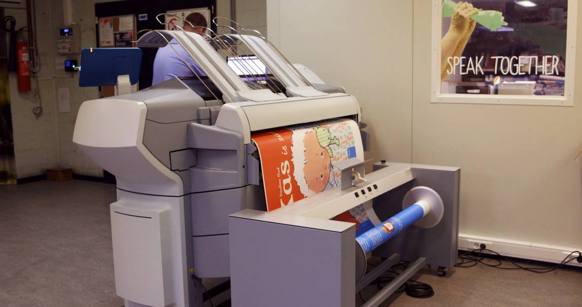 Commercial digital printer in an office prints an A1 sheet of paper with a cartoon image of a child on an orange background.