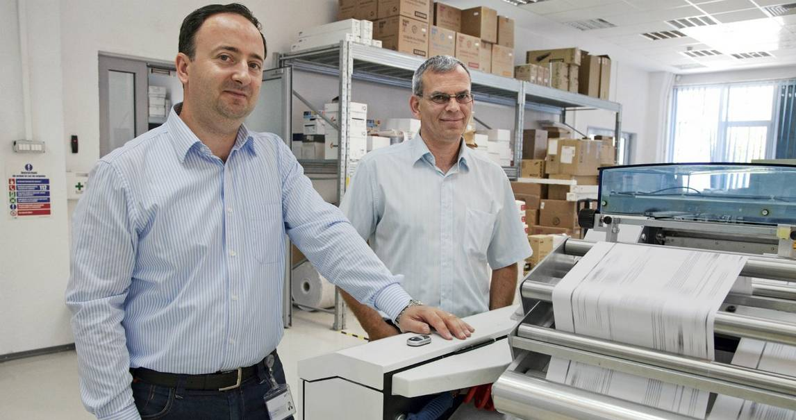 Two middle-aged men in light blue shirts and stand behind a commercial printer as reams of printed paper weave through the open-ended machine.
