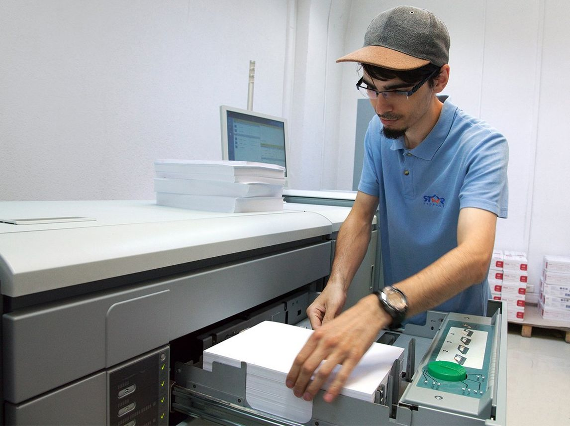Man in sky blue polo shirt and a baseball cap loads A4 paper into the open drawer of a large Canon digital printing press.