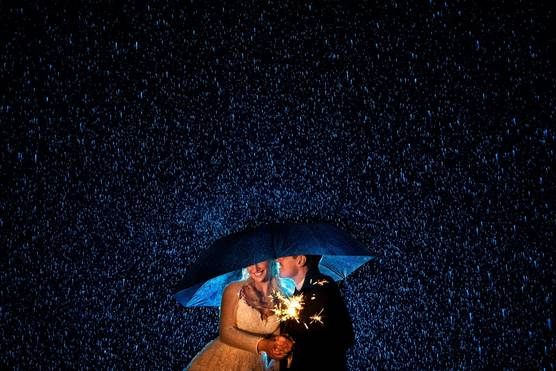 Newlyweds hold a sparkler while standing under an umbrella in the rain.