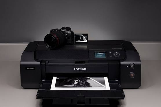 A Canon imagePROGRAF PRO-300 printer with a Canon camera on top and a print coming out onto its output tray.