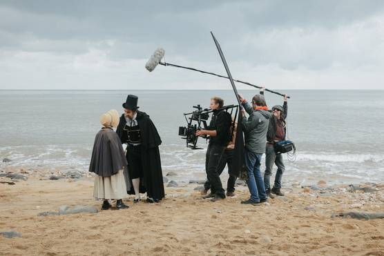 A camera crew filming two actors beside the sea: a Victorian gentleman in a top hat and cape leaning over to talk to a young girl.