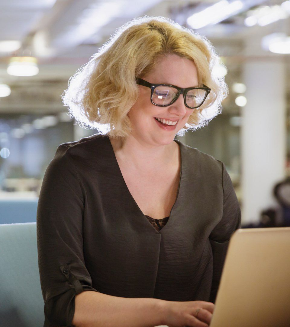 Blonde-haired woman in dark-rimmed glasses and khaki blouse smiles broadly as she looks at something on her laptop.