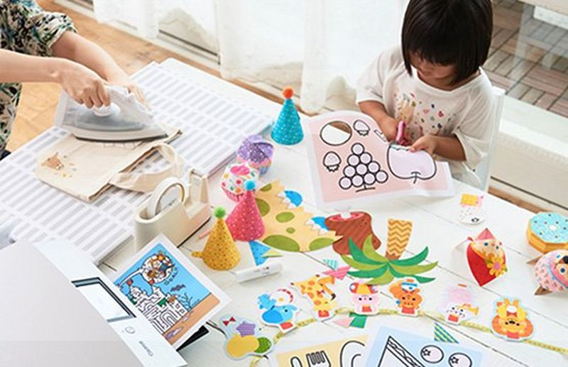 A child sat at a table with a parent creating colourful papercrafts using a Canon printer.